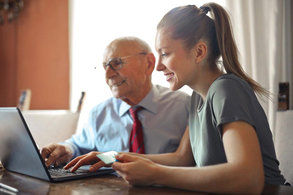 Hombre mayor y chica joven mirando un ordenador