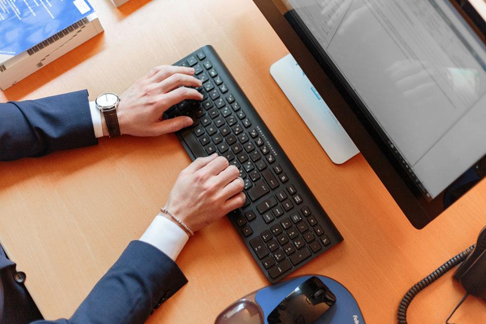 Manos de un hombre encima de un teclado. Vista zenital